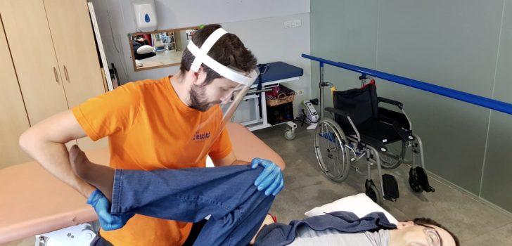Un fisioterapeuta amb una pantalla de protecció acompanya una persona amb paràlisi cerebral en els seus exercicis terapèutics